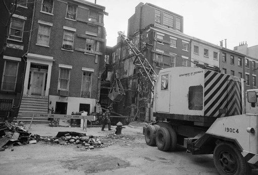 Workers clear rubble from the site of the townhouse explosion at 18 West 11th