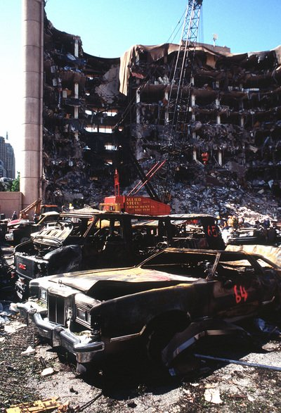 Ten bombings - The bombed remains of automobiles with the bombed Federal Building in the background.  The military is providing around the clock support since a car bomb exploded inside the building on Wednesday, April 19, 1995.