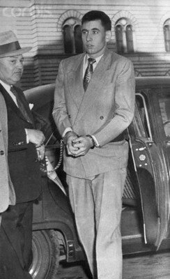 November 28, 1955,  an unidentified sheriff's deputy escorts the handcuffed John Gilbert Graham, 23, out of a car for his arraignment on charges of dynamiting a United Airlines DC-6B which exploded and crashed near Longmont, Colorado, November 1st, killing all 44 persons on board, including Graham's mother. He was given a two-week continuance while his attorneys, newly appointed by the court, have time to study the case. (Image © Bettmann/CORBIS)