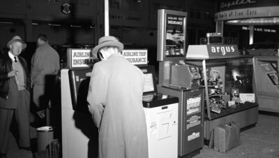 """Jack Graham used a similar machine to buy insurance policies on his mother's life. Travel Insurance Kiosks at Detroit's Willow Run Airport, 1954. Part of the """"Old News"""" collection at the Ann Arbor District Library."""