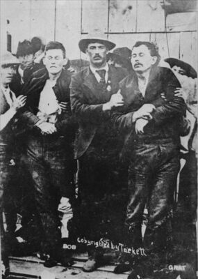 Law officers hold up the bodies of dead outlaws Bob (23) and Grat (31) after their attempted robbery in Coffeyville, Kansas (Kansas Memory)
