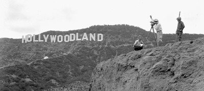 Surveyors standing east of the sign on top of Bronson Canyon measure the Hollywoodland sign with Mulholland Highway visible beneath it.