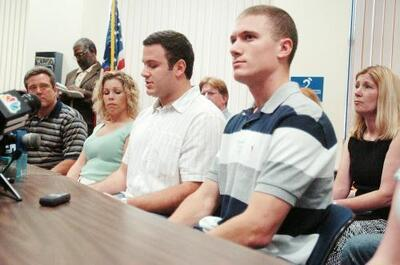 Two of the Polks' sons, Adam (C) and Gabriel (R)  at a press conference held after the jury announced its verdict