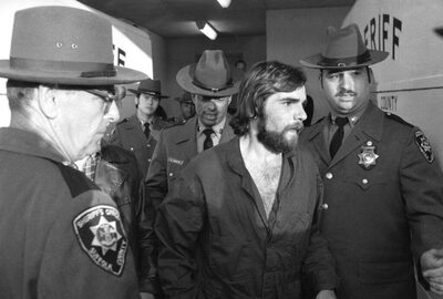 Deputies lead Ronald DeFeo out of a Long Island courtroom after a hearing in 1974 (AP)