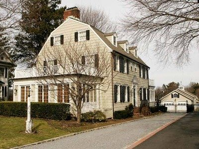 """A recent photo of the """"Amityville Horror"""" house, now 108 Ocean Avenue. Note the addition of the sunroom (foreground) and that the creepy """"eye"""" winodws have been replaced with square ones (SyFy.com)"""